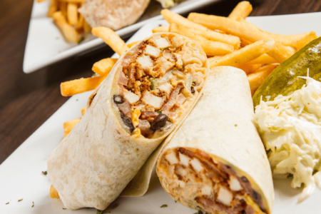 Southwest Chicken Wrap - Fried chicken, bacon, corn, blackbeans, lettuce, tomato, cheddar cheese & chipotle mayo, served with french fries, coleslaw, and a pickle
