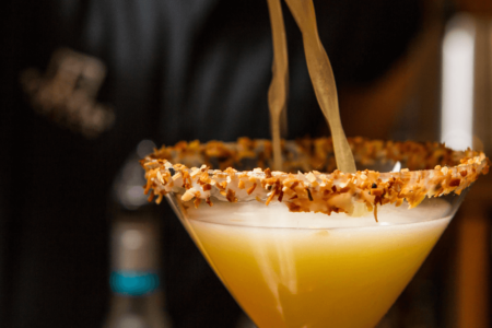 Pouring a Coconut Martini with Toasted Coconut Rim