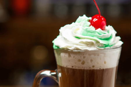 Irish Coffee Irish whiskey, hot coffee, whipped cream. Topped with green crème de menthe