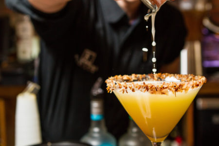 Pouring a Coconut Martini with a toasted coconut rim