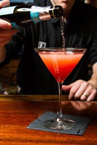 Adding champagne to Sparkling Blood Orange martini