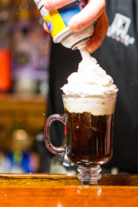 Putting whipped cream on top of coffee