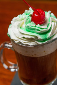 Irish Coffee topped with whipped cream and a cherry