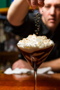 Sprinkling toasted almond topping on top of our Toasted Almond Martini