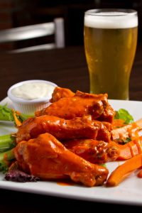 Plate of buffalo wings with beer behind