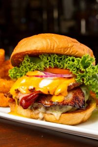 Bacon cheese burger garnished with lettuce, onions, and tomatoes
