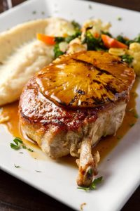 Karvers Pork Chop topped with a grilled pineapple, served with mashed potatoes and vegetables