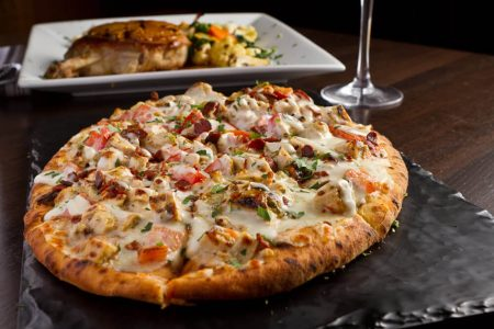 Chicken Bacon Ranch flatbread with Pork Chop plated behind it