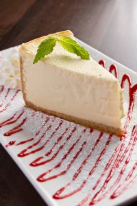Cheesecake plated with a raspberry drizzle