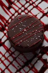 Vanilla & Chocolate Gelato Tartufo Raspberry & chopped walnut center, hand dipped in rich dark chocolate. Finished with a raspberry drizzle.