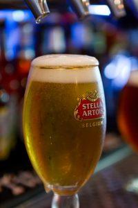 Stella Artois glass full of beer under tap