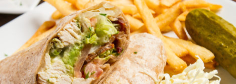Photo of our Chicken Avocado Wrap- Grilled chicken or shrimp, avocado, crispy bacon, swiss, lettuce, tomato & ranch dressing, served with french fries and a pickle