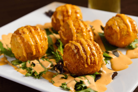 Photo of our Bacon & Cheddar Potato Balls - Coated in broccoli batter & bread crumbs & drizzled with chipotle ranch