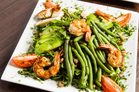 Photo of the Karvers Signature salad - Arugula, green beans, avocado, tomato, hearts of palm, candied walnut
